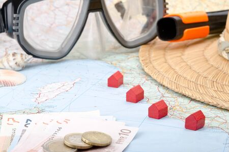 Toy houses on a map with euro banknotes, snorkel mask and seashells photo
