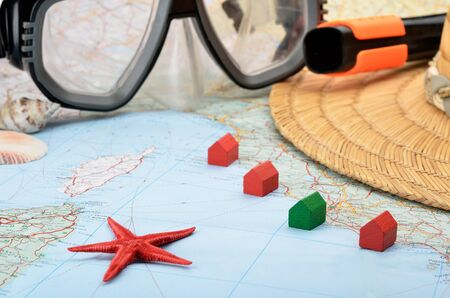 accomodation: Toy houses on a map with snorkel mask, seashells and starfish Stock Photo