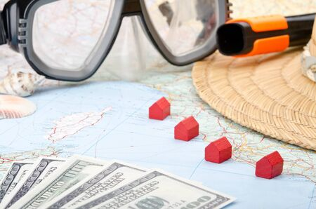 accomodation: Toy houses on a map with euro banknotes, snorkel mask and seashells