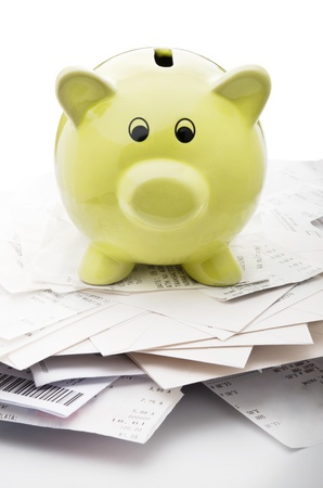 budget crisis: Piggy bank on top of stack of payed bills Stock Photo
