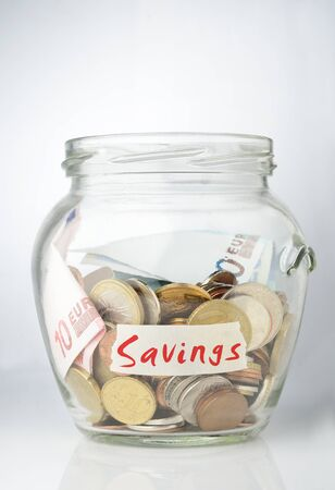 pennypinching: Savings jar full with coins Stock Photo