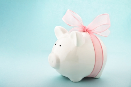 Cute piggy bank with pink bow and ribbon. Side view photo