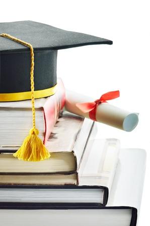 birrete: Casquillo y diploma en la parte superior de la pila de libros
