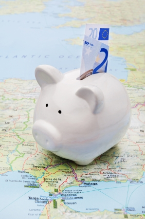 holiday budget: Piggy bank on top of a map symbol of world economy or holiday savings