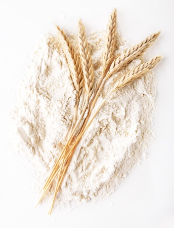 fascicle: Ears of wheat on a flour heap Stock Photo