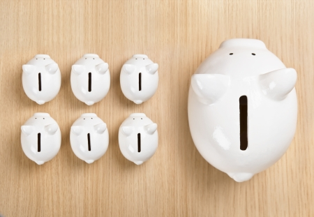 Piggy bank standing out from row Stock Photo