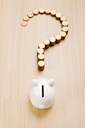 financial questions: Question mark sign made out of coins in front of a piggy bank Stock Photo