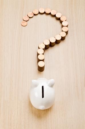 leu: Segno di punto interrogativo fatto di monete di fronte a un salvadanaio