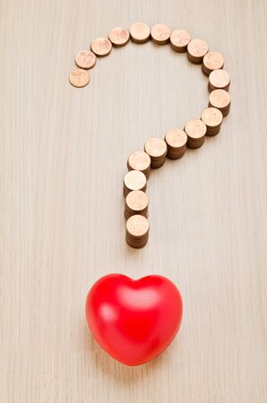quality questions: Question mark sign made out of coins and red heart
