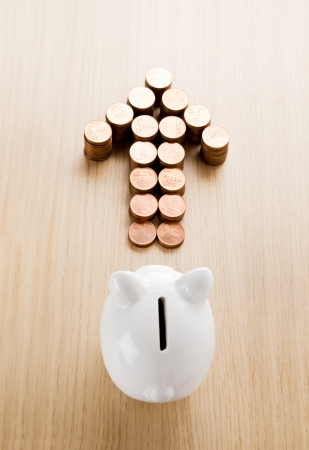ron: Arrow made out of coins in front of a piggy bank Stock Photo
