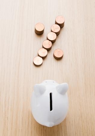 Percentuale segno fatto di monete di fronte a un salvadanaio