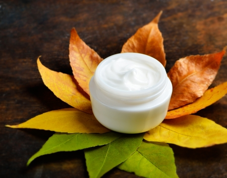 antiaging: Anti-aging cream on a background of green and dry leaves