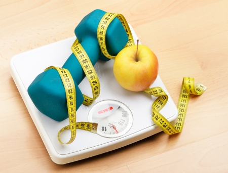 weighting: Fresh apple and dumbbells tied with a measuring tape on a weighting scale