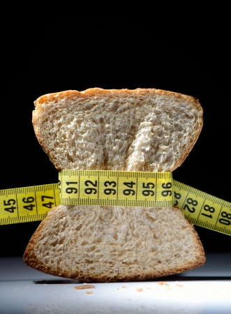 Piece of bread grasped by measuring tape with dark background Stock Photo - 20954899