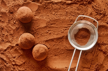 Rolling chocolate truffles in cocoa powder photo