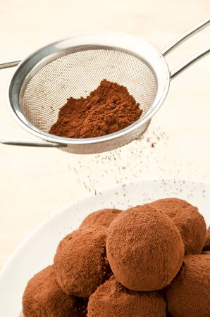 Cocoa powder being sprinkled from a sieve over bowl of chocolate truffles photo