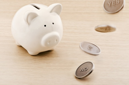 Piggy bank looking to a flipping coin Stock Photo - 21524680