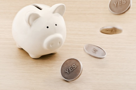 Piggy bank looking to a flipping coin photo