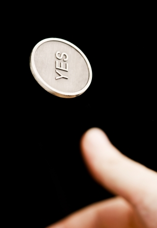 coin toss: Hand flipping an yesno coin on black background Stock Photo