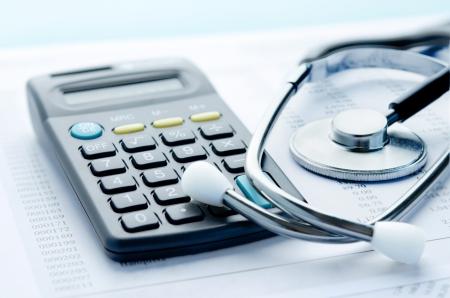 電卓: 医療費や医療保険医療費の聴診器とお金のシンボル 写真素材