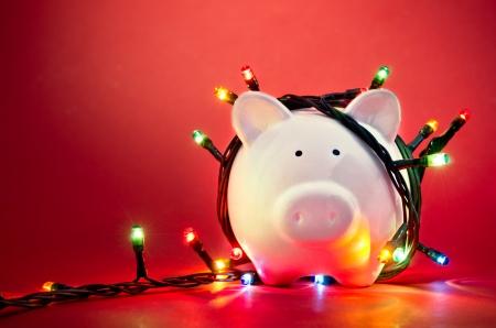 Salvadanaio avvolta in luci della stringa di Natale