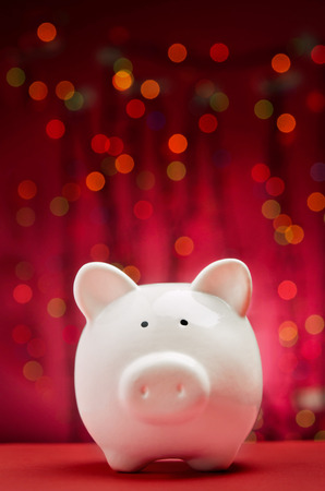savings problems: Piggy bank with Christmas lights background Stock Photo