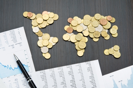 Office desk with world map made of money coins and report sheets