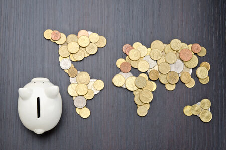 bank economic crisis: Office desk with world map made of money coins and piggy bank Stock Photo