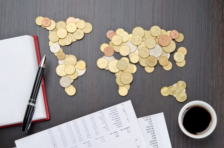 international money: Office desk with world map made of money coins and agenda