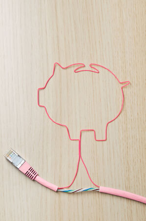 Electronic banking. Pink cable shaping a piggy bank photo