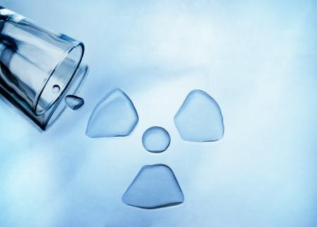 kwaśne deszcze: Zanieczyszczenie wody. Szklanka wody wylany kształcie znaku radioaktywnych Zdjęcie Seryjne