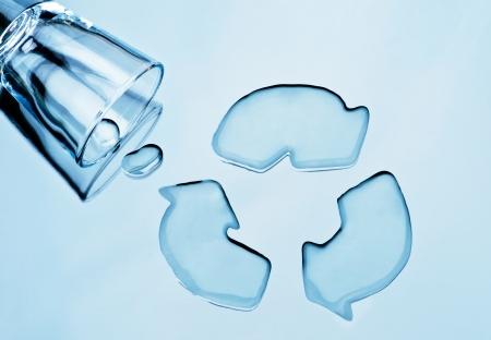kwaśne deszcze: Recyklingu wody. Szklanka wody wylany kształcie symbolem recyklingu