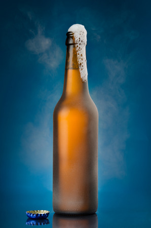 Open beer bottle on blue background