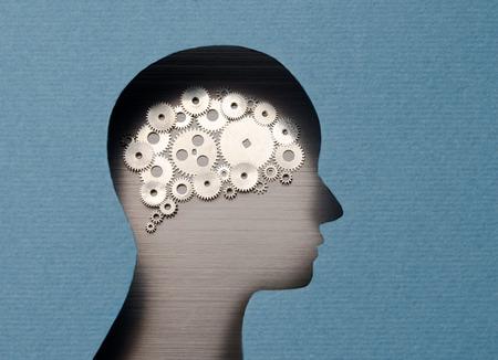 Pensare meccanismo. Testa umana con il cervello a forma di ingranaggi