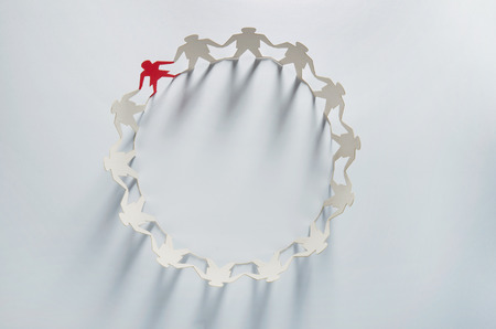 Circle of white business men paper cut-out figures with red woman leader standing out from the crowd photo