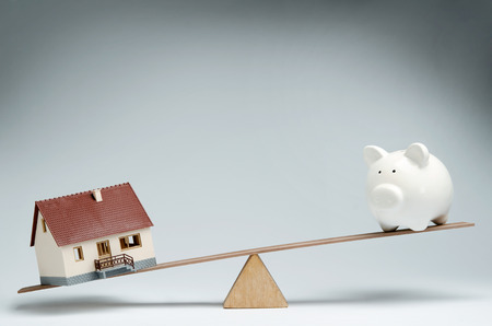 mortgage rates: Home loans market  Model house and piggy bank balancing on a seesaw Stock Photo