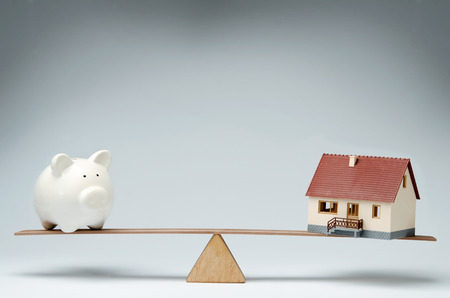 Home loans market  Model house and piggy bank balancing on a seesaw Stock Photo