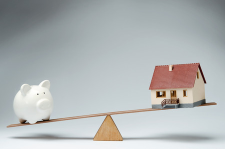 Home loans market  Model house and piggy bank balancing on a seesaw Banco de Imagens