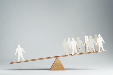 Men balanced on seesaw over a single man photo