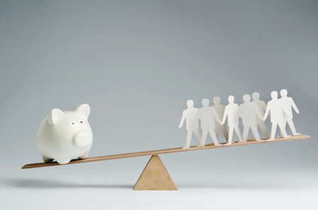 credit union: Men balanced on seesaw over a piggy bank