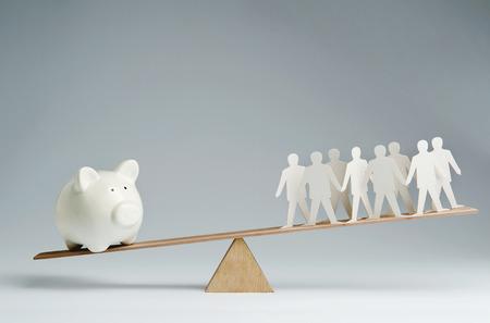 Men balanced on seesaw over a piggy bank