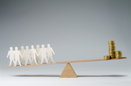 social work: Men balanced on seesaw over a stack of coins Stock Photo