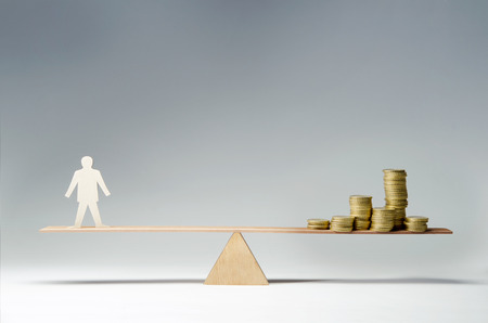 seesaw: Man balanced on seesaw over a stack of coins Stock Photo