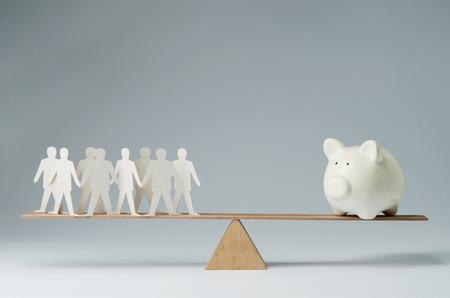 la union hace la fuerza: Hombres equilibrados en el balancín sobre una alcancía