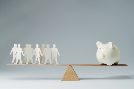 Men balanced on seesaw over a piggy bank photo