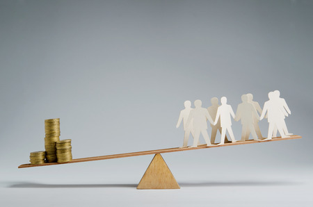 credit union: Men balanced on seesaw over a stack of coins Stock Photo