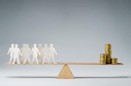 Mannen evenwichtig op wip over een stapel van munten Stockfoto