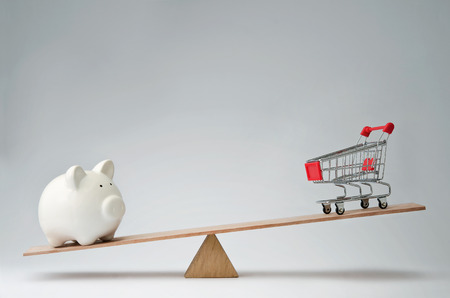income market: Shopping trolley and piggy bank balancing on a seesaw Stock Photo