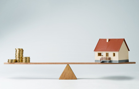 heavy risk: Model house and money coins balancing on a seesaw