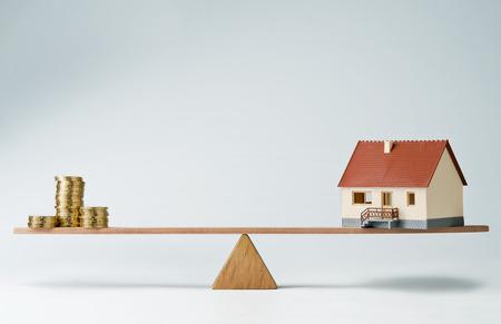 Model huis en geld munten balanceren op een wip Stockfoto